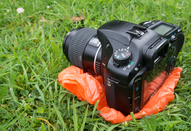 Pentax K-5 on shopping bag to protect from wet grass